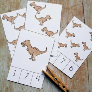 t rex count and clip cards with clothespin on a wooden table each card had a picture or few of trex dinosaur and then numbers to match below