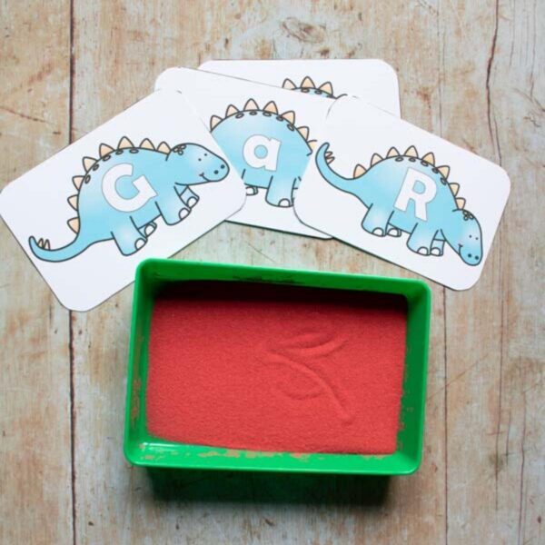 Dinosaur Alphabet Cards from the Rainy Day Mum Print and Play store in use with a sand tray